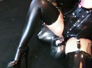 Domina Lady Vampira erteilt der Rubberdoll die Aufgabe, ihr die High Heels anzuziehend. Kniend vor der Herrin zittert der Sklave beim Anblick dieser Amazone in Latex. Der enge Latexbody ist zu klein für die riesigen Naturtitten mit den Nippelpiercings, aber genau richtig für das Tease and Denial Spiel der Latexdiva. Der Sklave soll sich auf den Boden legen, dann werden die Füße an der Seilwinde fixiert. Hilflos hängt er gleich gefesselt in der Luft. Die strenge FemDom über ihm. Er spürt die High Heels an seinen Eiern, dann Schläge auf den Arsch. Das kleine Gummiobjekt wird beim Facesitting erneut zum Lustsklaven der Mistress.und darf ihre göttlichen Füße verehren...